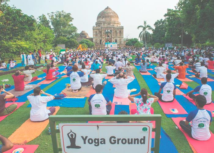 Энтузиасты йоги участвуют в утренней сессии напротив средневекового памятника Сады Лоди в Нью-Дели 21 Июня 2016.
