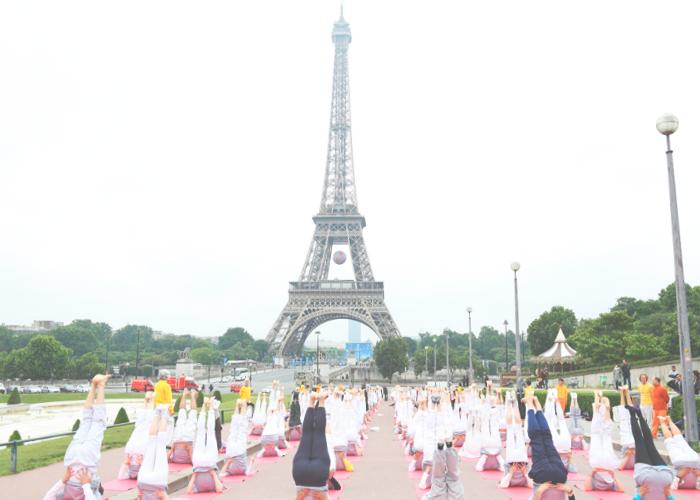 Йога энтузиасты на фоне Эйфелевой башни в Париже.