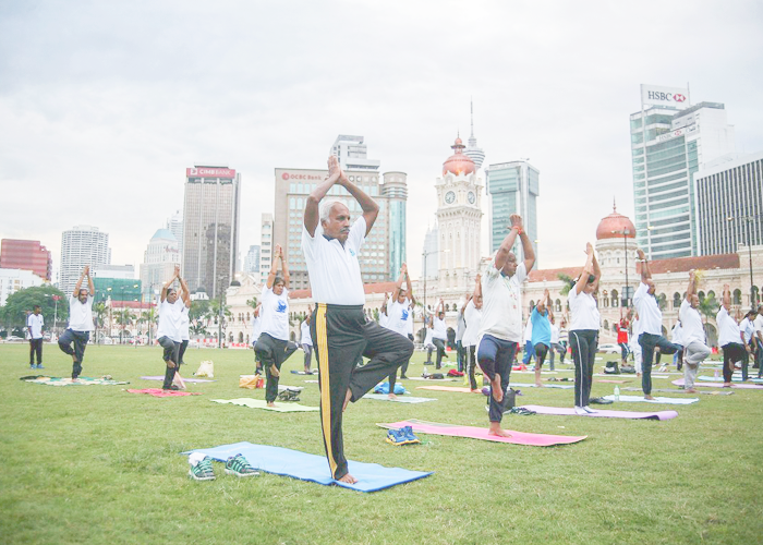 Любители йоги участвуют в коллективных упражнениях на площади независимости Датаран Мердика, Куала-Лумпур в Малазии.